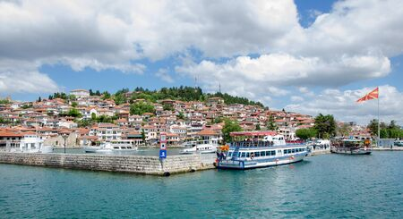macedonian flag: View of Ohrid old city and Ohrid lake (the most popular and most visited landmark in Macedonia) with waving Macedonian flag and several boats