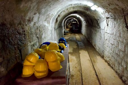 hard hats: Table with yellow hard hats at entrance to a mine with an arched tunnel stretching into the distance and a small gauge railway track for bringing material to the surface