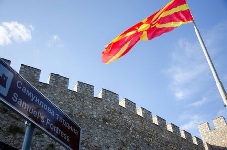 macedonian flag: Walls and towers of medieval fortress with waving macedonian flag on pole and sign with label Samuels Fortress, Ohrid, Macedonia Stock Photo