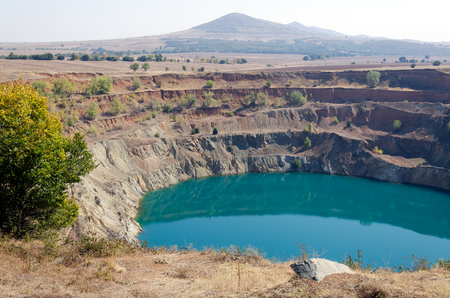 Deserted opencast mine pit partially full of water
