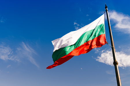 Agitant le drapeau bulgare contre le ciel bleu profond