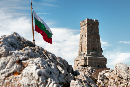 National memorial monument on Shipka peak, Bulgaria and waving Bulgarian flag Stok Fotoğraf