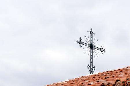 Religiöser Hintergrund des Eisenkreuzes auf rotem Ziegeldach gegen den bewölkten Himmel mit Kopienraum