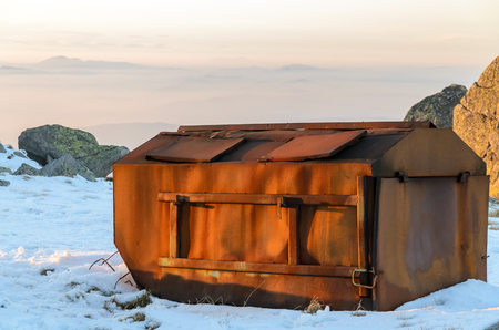 Old rusty container for garbage collection in the mountain