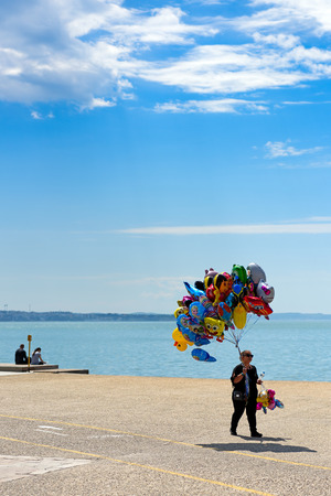 Thessaloniki, Greece - April 14, 2017 : Woman with colorful balloons for sale walking along Thessaloniki seafront Editorial