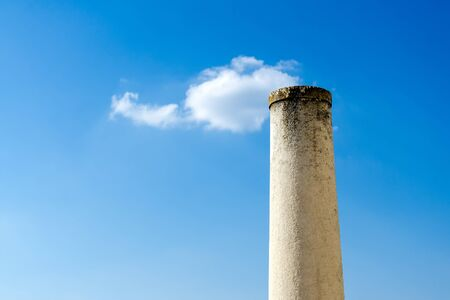 Stone column with small puffy cloud on top against blue sky