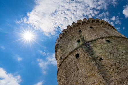 Low angle view of The White Tower on bright sunny day with sunbeams in the blue sky, Thessaloniki, Greece