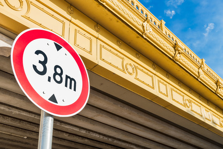 Circular low bridge regulatory road sign with red ring showing the height limit on non-arch yellow bridge against blue sky Stock Photo