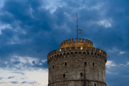 The Ottoman White Tower of Thessaloniki, symbol of Thesalonika, Macedonia, Greece with waving Greek flag on top at night
