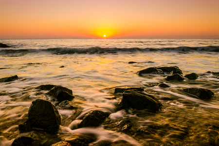 Seascape sunrise long exposure with water flowing between small rocks and golden toned water and sky
