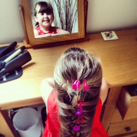 rapunzel: Adorable little girl with flowery French braid facing mirror Stock Photo