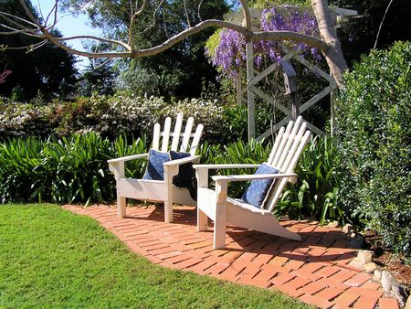 uplifting: A lovely landscaped garden setting with two empty deck chairs.