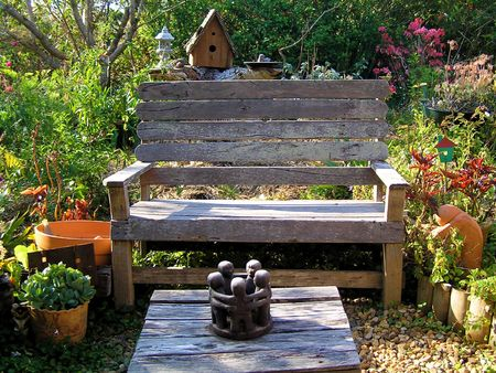containing: A cute garden setting containing old wooden furniture, various plants and flowers, and decorative ornaments.