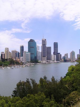population growth: A view of brisbane city from across the river near Kangaroo Point with lots of lush greenery around.