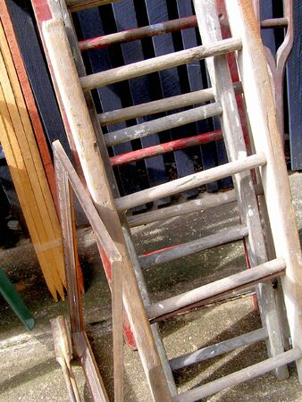Old and unwanted quaint wooden ladders and various items sit outside at a garage sale, waiting for someone to buy them.  photo