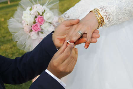 Groom wears a wedding ring to the bride