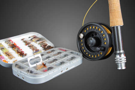A box with artificial flies and fishing rod and reel on a black background Stock Photo - 14002874