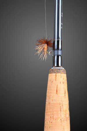 Fly-fishing rod with a fly on the line on a black background