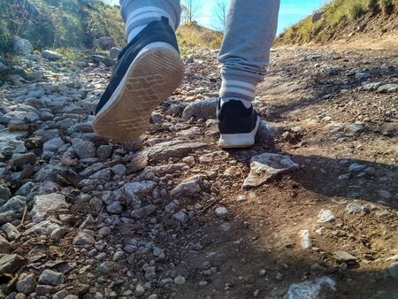 Closeup of male sport shoes and legs while running in nature on a rocky difficult terrain. Looking for journey in a natural environment