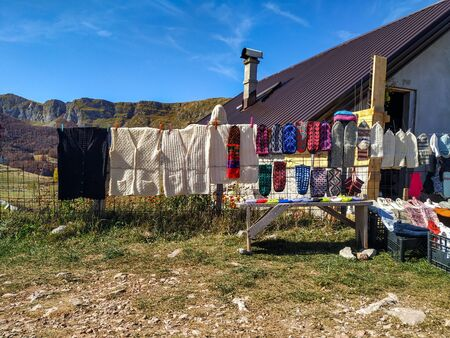 Local wool socks products in the mountain being sold by villagers on sunny autumn day presented on fence, wooden bench and mountain cottage. Stock Photo