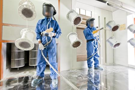 metales: Trabajador vistiendo ropa protectora realizar revestimiento en polvo de detalles de metal en una cámara industrial especial