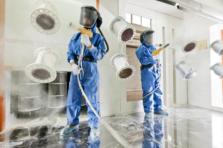 特殊な工業用カメラの金属パーツの粉体塗装を実行する防護服を身に着けている労働者 写真素材