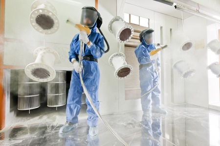 Worker wearing protective wear performing powder coating of metal details in a special industrial camera Archivio Fotografico