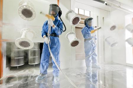 festékek: Worker viselése védőfelszerelés végző porszórt fém részleteket egy speciális ipari kamera