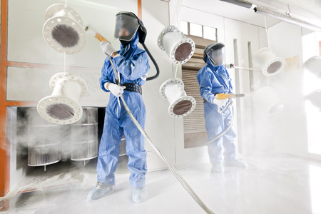 Worker wearing protective wear performing powder coating of metal details in a special industrial camera Imagens