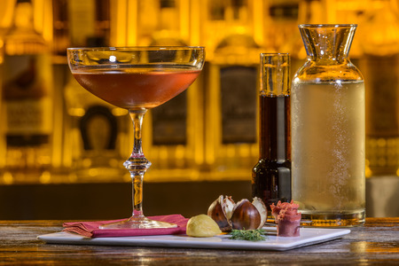 liqueurs: Coctail, on a wooden table, with wooden cupboard in the background. Stock Photo