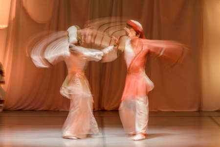 sufi: Whirling Dervishes in white and in a religious trance performing on a Turkish stage.