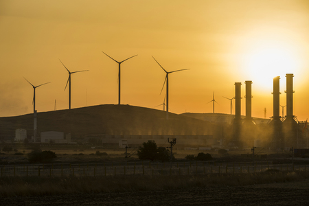 Silhouettes of two wind energy turbines in the sunset with red sky Stock fotó