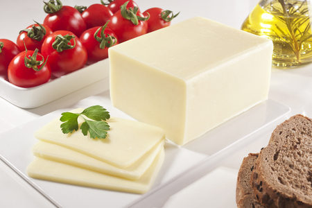 A block of cheddar cheese and cheese slices with a cheese slicer.