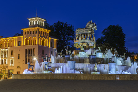 kutaisi: Kutaisi, Georgia - May 5, 2013: Detail from the central square in Kutiasi. People are looking at water fountain, taking pictures or sitting on its edge. In centre is fountain while in background are some buildings and trees from park. Above everything is  Editorial