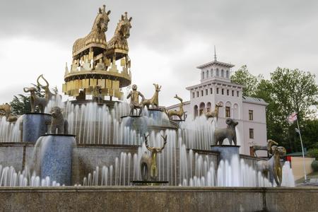 kutaisi: Kutaisi, Georgia - Dettaglio da piazza centrale di Kutiasi. Le persone sono alla ricerca di fontana di acqua, scattare foto o seduto sul bordo. Al centro si trova la fontana, mentre in fondo sono alcuni edifici e alberi da parco. Sopra tutto � cielo blu.