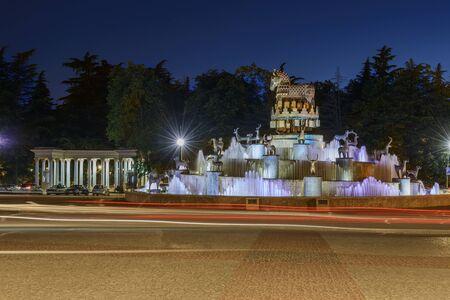 personas tomando agua: Kutaisi, Georgia - 5 de mayo de 2013: Detalle de la plaza central en Kutiasi. La gente está buscando en la fuente de agua, la toma de fotografías o sentado en su borde. En el centro está la fuente, mientras que en el fondo son algunos de los edificios y los árboles del parque. Por encima de todo está