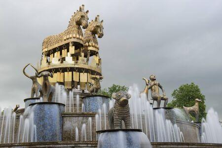 personas tomando agua: Kutaisi, Georgia - Detalle de la plaza central en Kutiasi. La gente est� buscando en la fuente de agua, la toma de fotograf�as o sentado en su borde. En el centro est� la fuente, mientras que en el fondo son algunos de los edificios y los �rboles del parque. Por encima de todo est� el cielo azul.