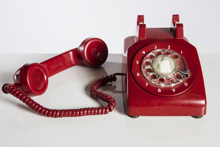 old fashioned rotary phone: Retro red dial phone isolated on white. Stock Photo