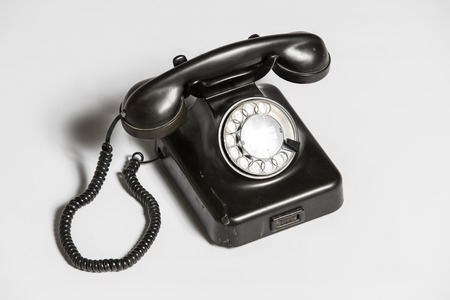 old fashioned rotary phone: Old black telephone isolated on white