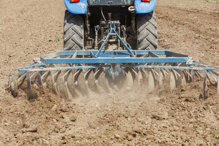 ploughing: Tractor ploughing on the field in sunlight