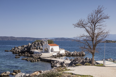 In North Chios and shortly after Sykiada village lies the picturesque chapel of Agios Isidoros (St. Isidore). It is a bay with beach with fine pebbles which leads to the chapel.  It is one of the most photographed places on the island. Behind the church t Stock fotó - 79828894