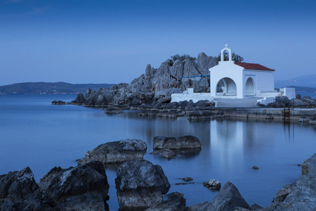 In North Chios and shortly after Sykiada village lies the picturesque chapel of Agios Isidoros (St. Isidore). It is a bay with beach with fine pebbles which leads to the chapel.  It is one of the most photographed places on the island. Behind the church t Stock fotó - 80099327