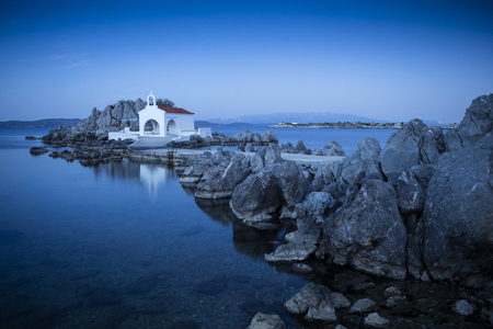 In North Chios and shortly after Sykiada village lies the picturesque chapel of Agios Isidoros (St. Isidore). It is a bay with beach with fine pebbles which leads to the chapel.  It is one of the most photographed places on the island. Behind the church t Stock fotó - 80167894
