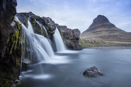 Kirkjufell is a free standing mountain of the Snaefellsnes peninsula, on the northern coast of Iceland. Together seen with the mountain, is a waterfall called Kirkjufellsfoss that flows into the sea. Stok Fotoğraf