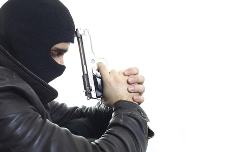 leaned: A thief in balaclava holding a gun leaned to his forehead, isolated on a white background