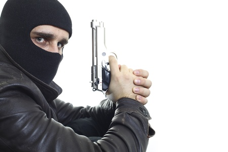 death head holding: A thief in balaclava holding a gun and looking to camera, leaned on a wall, isolated on a white background