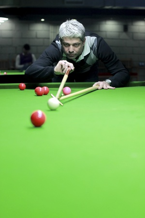A snooker player is just about to hit the ball