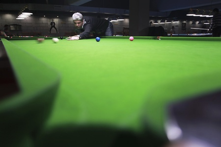 Low angle view of a snooker player in an entertainment center Фото со стока