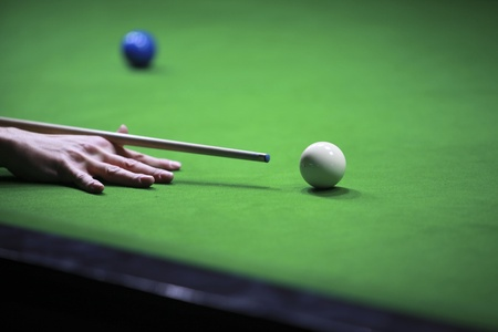Close up shot of a snooker player hitting the white ball