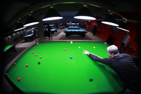 A snooker player shot from above with a fisheye lens